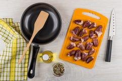 Ruwe kippenharten op scherpe raad, pan, olie, specerij stock foto's
