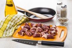 Ruwe kippenharten op scherpe raad, pan, olie, specerij royalty-vrije stock afbeeldingen