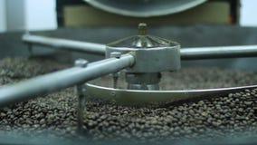 Ruwe koffiebonen, die op een grote broodroostermachine roosteren stock videobeelden