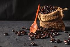 Ruwe koffiebonen in een zakzak op een zwarte achtergrond royalty-vrije stock foto