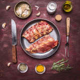 Ruwe lamsribben op een pan, met een mes en een vork voor de vlees, kruiden en kruiden houten hoogste mening rustieke als achtergr Stock Afbeelding