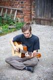 Ruwe landkerel die zijn gitaar speelt Stock Foto's