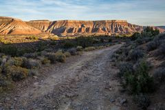 Ruwe landweg onder woestijnmesas bij zonsondergang royalty-vrije stock afbeelding