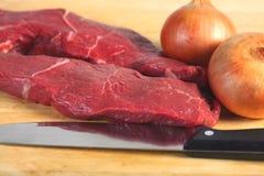 Ruwe lapje vlees en uien Stock Fotografie