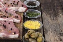 Ruwe lapjes vlees met kruiden op een houten oppervlakte Stock Fotografie