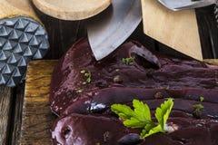 Ruwe lever met kruiden en keukenbestek Stock Foto's