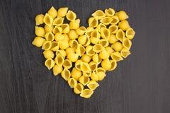 Ruwe macaroni - conchiglie deegshells in de vorm van een hart op een donkere achtergrond stock afbeeldingen