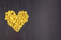 Ruwe macaroni - conchiglie deegshells in de vorm van een hart op een donkere achtergrond royalty-vrije stock foto