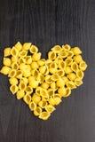 Ruwe macaroni - conchiglie deegshells in de vorm van een hart op een donkere achtergrond stock foto's