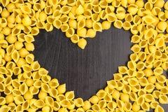 Ruwe macaroni - conchiglie deegshells In het midden van de lege ruimte in de vorm van een hart op een zwarte achtergrond stock fotografie