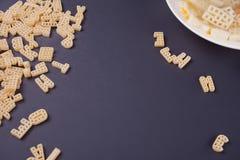 Ruwe macaroni en plaat met soep op zwarte achtergrond royalty-vrije stock foto's