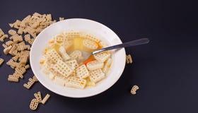 Ruwe macaroni en plaat met soep op zwarte achtergrond stock fotografie