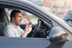 Ruwe mens die zijn auto drijven en op de telefoon spreken Royalty-vrije Stock Foto