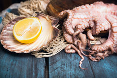 Ruwe Octopus en citroen op blauwe houten lijst Stock Fotografie