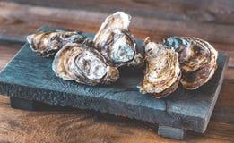 Ruwe oesters op de raad stock foto