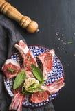 Ruwe ongekookte lamskoteletten met kruiden en kruiden op kleurrijke plaat over donkere houten achtergrond Royalty-vrije Stock Fotografie