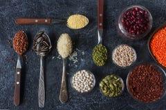 Ruwe organische graankorrels, zaden en bonen in houten lepels en kommen Royalty-vrije Stock Foto