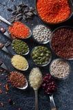 Ruwe organische graankorrels, zaden en bonen in houten lepels en kommen Stock Foto