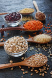 Ruwe organische graankorrels, zaden en bonen in houten lepels en kommen stock afbeeldingen