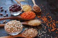 Ruwe organische graankorrels, zaden en bonen in houten lepels en kommen Stock Afbeelding