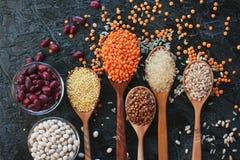 Ruwe organische graankorrels, zaden en bonen in houten lepels en kommen Stock Foto's