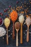 Ruwe organische graankorrels, zaden en bonen in houten lepels en kommen Stock Fotografie
