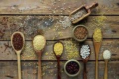 Ruwe organische graankorrels, zaden en bonen in houten lepels op rustieke houten achtergrond stock afbeelding