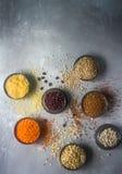 Ruwe organische graankorrels, zaden en bonen op donkere steenachtergrond, ruimte voor tekst Stock Foto's