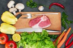 Ruwe organische groenten met verse ingredi?nten voor het gezonde koken op donker backgroundRawvlees Ruw rundvleeslapje vlees op w stock foto's