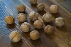 Ruwe organische okkernoten in shell op oude bruine houten achtergrond in rustieke stijl Oogstnoten van land Gezonde ingrediënten stock afbeelding