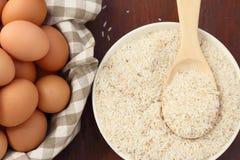 Ruwe rijst met lepel en ei Royalty-vrije Stock Afbeeldingen