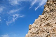 Ruwe rots met scherpe randen en zachte wolken, zoals veren op een blauwe hemel Royalty-vrije Stock Foto's