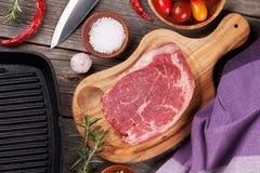 Ruwe rundvleeslapje vlees en kruiden op houten lijst Stock Afbeeldingen