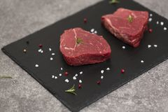 Ruwe rundvleeslapje vlees en kruiden op leiraad Ruw vlees op zwarte achtergrond royalty-vrije stock afbeeldingen