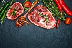 Ruwe rundvleeslapjes vlees met kruiden en rozemarijn Vlak leg Hoogste mening Royalty-vrije Stock Foto's