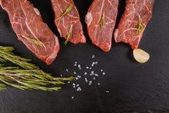 Ruwe rundvleeslapjes vlees met kruiden en rozemarijn Vlak leg stock foto's