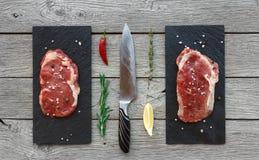 Ruwe rundvleeslapjes vlees op donkere houten lijstachtergrond, hoogste mening Royalty-vrije Stock Foto's