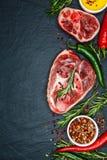 Ruwe sappige vleeslapjes vlees klaar voor het roosteren en vegatables op een bla Stock Afbeeldingen