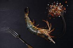 Ruwe shrims met kruid op zwarte royalty-vrije stock foto