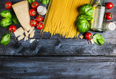 Ruwe spaghetti met tomaten, basilicum, parmezaanse kaas en olie, kokende Ingrediënten op blauwe rustieke houten achtergrond, hoog Royalty-vrije Stock Afbeelding