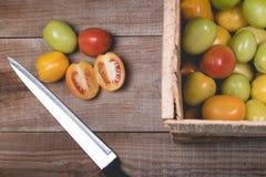 Ruwe Tomaten op een houten achtergrond Stock Afbeeldingen