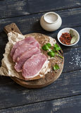 Ruwe varkenskoteletten en kruiden op een rustieke houten scherpe raad Stock Foto's