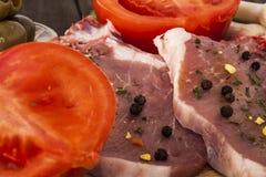 Ruwe varkenskoteletten en verse tomatenclose-up Royalty-vrije Stock Fotografie