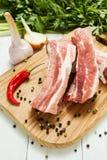 Ruwe varkensvleesribben met lagen van vet met groenten en peper op een scherpe raad royalty-vrije stock foto