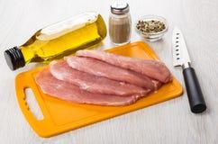 Ruwe varkensvleesschnitzel op scherpe raad, olie, peper, specerij, kni stock fotografie