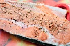 Ruwe verse filet van rode vissen bestrooide zwarte peper royalty-vrije stock afbeeldingen