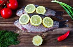 Ruwe vissen met een citroen en groenten Royalty-vrije Stock Afbeeldingen