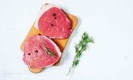 Ruwe vlees en rozemarijn op witte houten raad Vers rundvlees Klaar aan het roosteren Stock Afbeeldingen