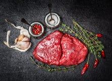 Ruwe vleeslapje vlees en ingrediënten voor het smakelijke koken op zwarte rustieke achtergrond Royalty-vrije Stock Afbeeldingen