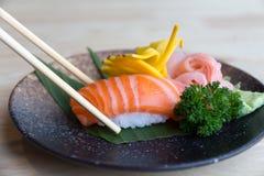 Ruwe zalm op rijst met eetstokjes - Japans voedsel royalty-vrije stock afbeelding